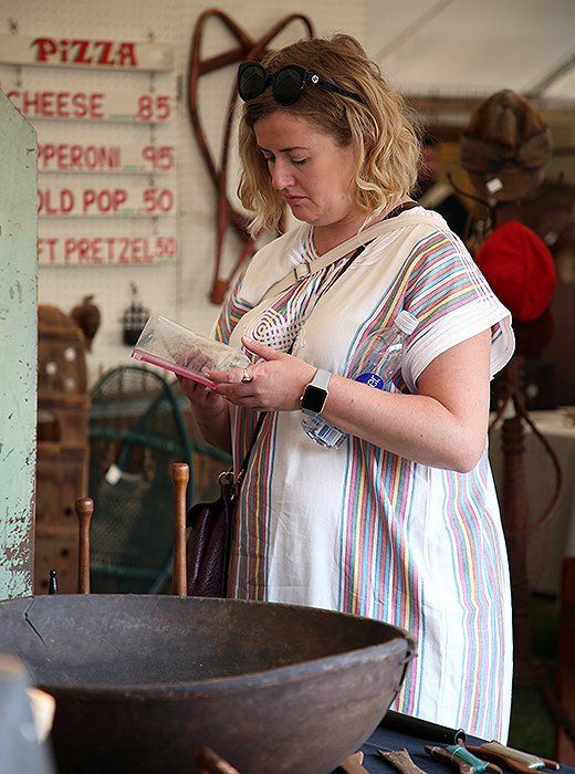 At Brimfield, stylist Eileen Behnke takes a closer look at a set of vintage tarot cards before deciding to pull the trigger. Photo by Taylor Swaim.