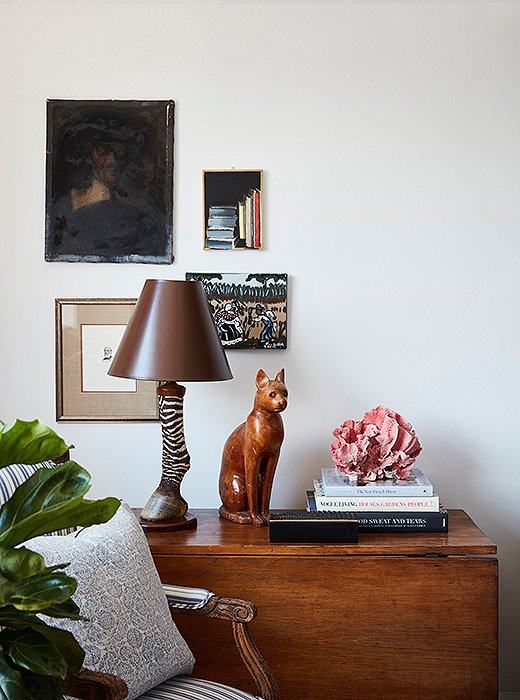 A lamp found at a thrift store13 years ago guides the eye toward artworks in an offhand grouping.