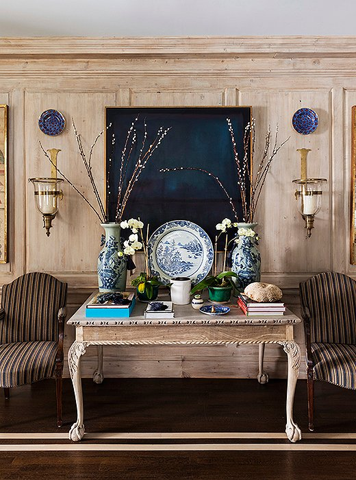 An oak ball-and-claw table matches the light-tone stripes on the stained wood floors, while pieces of blue-and-white pottery pop against an abstract painting in indigo hues. At night, visual romance emanates from flickering candles in the glass hurricane sconces.