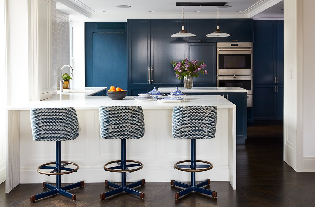 A trio of blue-and-white barstools accented with brass complement the rich navy-blue cabinetry.