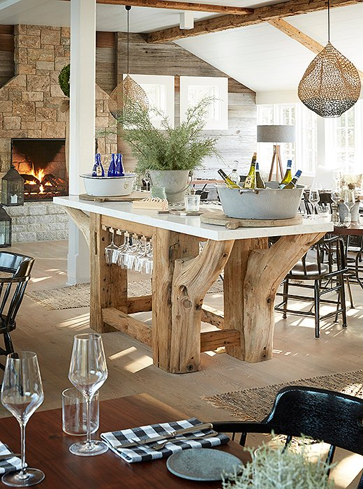 A custom island acts as a wine station amidst tables laid with handcrafted plates and black-and-white gingham linens.