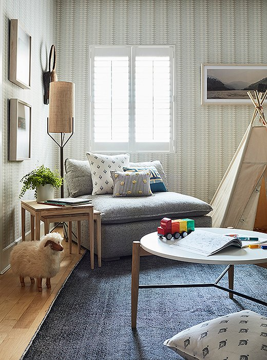 Off to one corner stands a stray lamb, anchoring two nesting tables and a midcentury-style lamp.