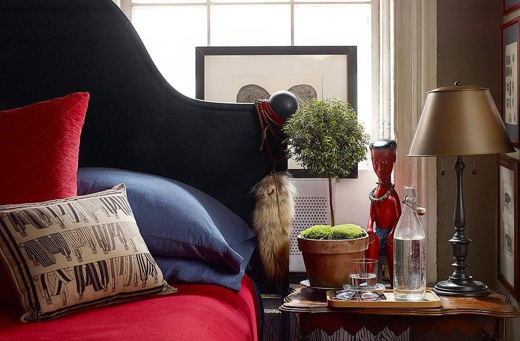 In the bedroom, an iron bed from Ralph Lauren Home is made with sheets that match the hue of the kitchen shelves. At bedside, an African statue stands guard just behind a cork tray holding spectacles, a glass (half full), and a small topiary.