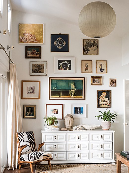 The master bedroom's gallery wall begins at the top of a lacquered vintage chest and ends at the ceiling. Featured works include a photograph taken by Paula on her honeymoon, gifts from friends, and vintage finds.