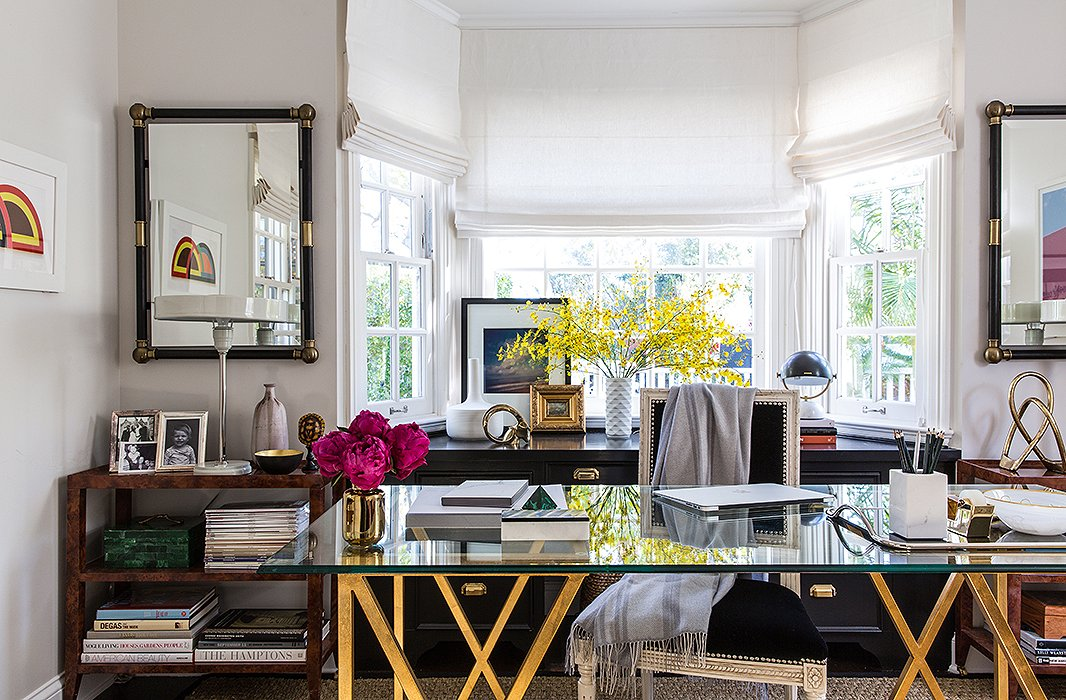 A healthy mix of style periods: The French traditionalism of a Louis XV-style chair, with whitewashed trim, sets off the modern lines of the glass desk. On each wall hangs a colorful mod artwork.