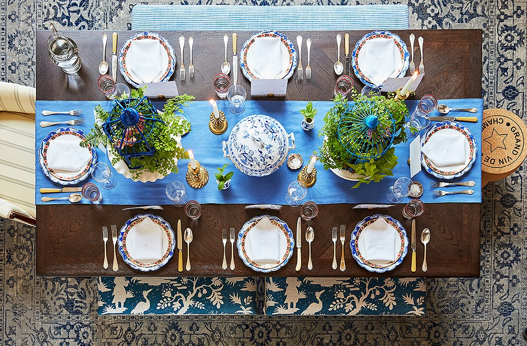The extendable dining table serves as the focal point of the multitasking space: By day it's a desk, and by night it's a table for a crowd. Stephanie's existing armchair, striped bench, and cork stool were a perfect match for the new dusty blue rug and benches upholstered in an oversize chinoiserie print. Featuring a medley of vintage plates, French flatware, and brass accents, the tablescape showcases Stephanie's love of blue and white—and her penchant for mixing old and new.