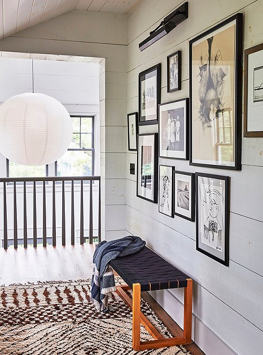 The upstairs gallery wall features a collection of black-and-white works, many of them gifts. A vintage Beni Ourain rug adds tonal texture.