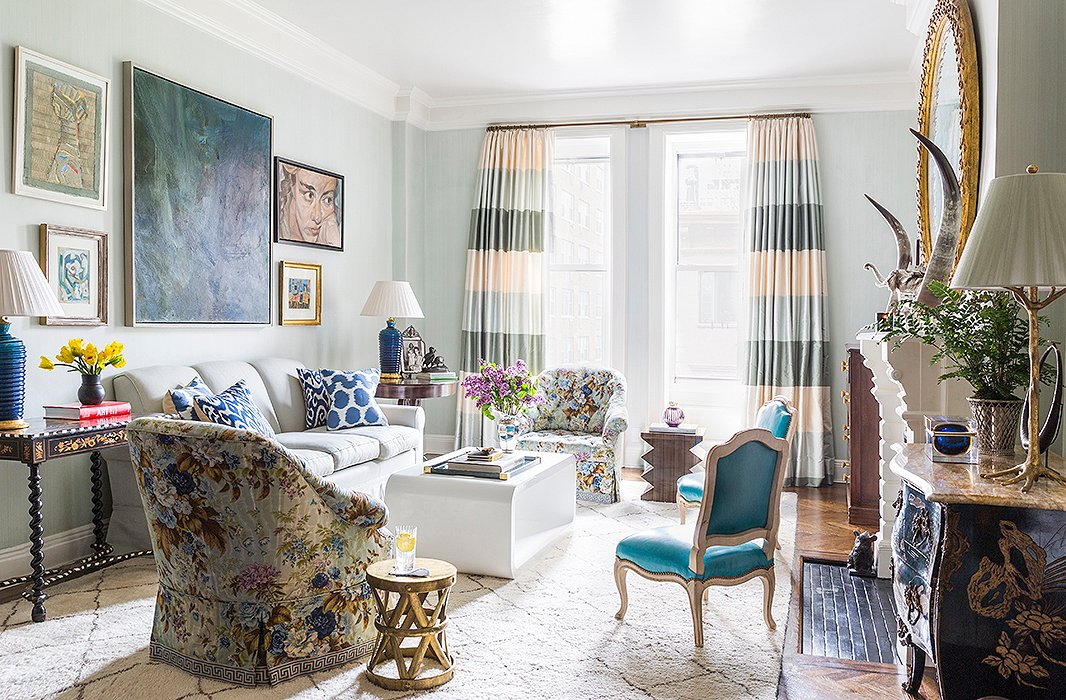 "In the living room, CeCe aimed to emphasize the apartment's connection to the green space nearby. ""We have this beautiful view of the treetops because we're on the fourth floor and of the skyline because all the buildings around us are low."" An airy blue wall color (a custom-mixed French strié) helps blur the boundaries between indoors and out, and curtains with a broad horizontal stripe visually widen the narrow windows."