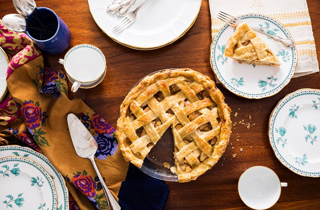 """Laying out the pie, along with pieces destined for the Thanksgiving table: a blue cup made by a ceramist friend on Nantucket, a set of green-and-white Spode china given to me by my mother-in-law, and a table linen from my great-grandmother with her monogram, """"M.H."""""""