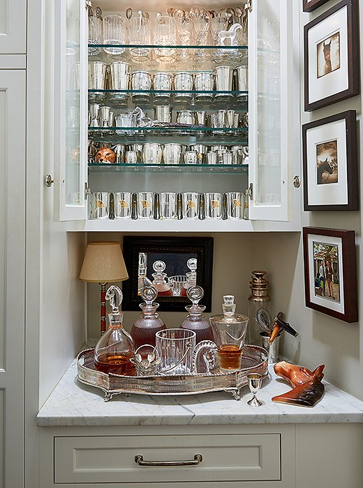 "Off the living room is a closet complete with a bar just for bourbon. Silver sipping cups and crystal tumblers above decanters of Maker's Mark and Bulleit glisten when lit. ""It certainly makes getting dressed a whole lot more fun,"" laughs Jon."