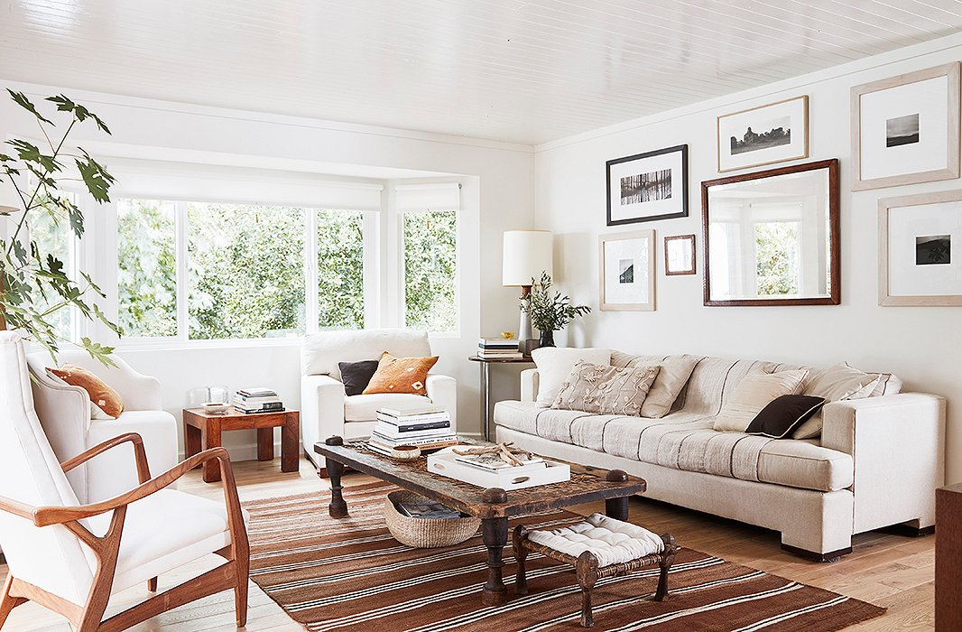 A careful curation of old and new gives the neutral living room vibrancy and life. In the corner, a Scandinavian lamp sits atop a Marcel Breuer table adjacent to an antique beveled mirror and art by Cloud, Laura, and Louis Conner. An antique Nepali daybed functions as the coffee table, mimicking the hues found in the Turkish kilim below.