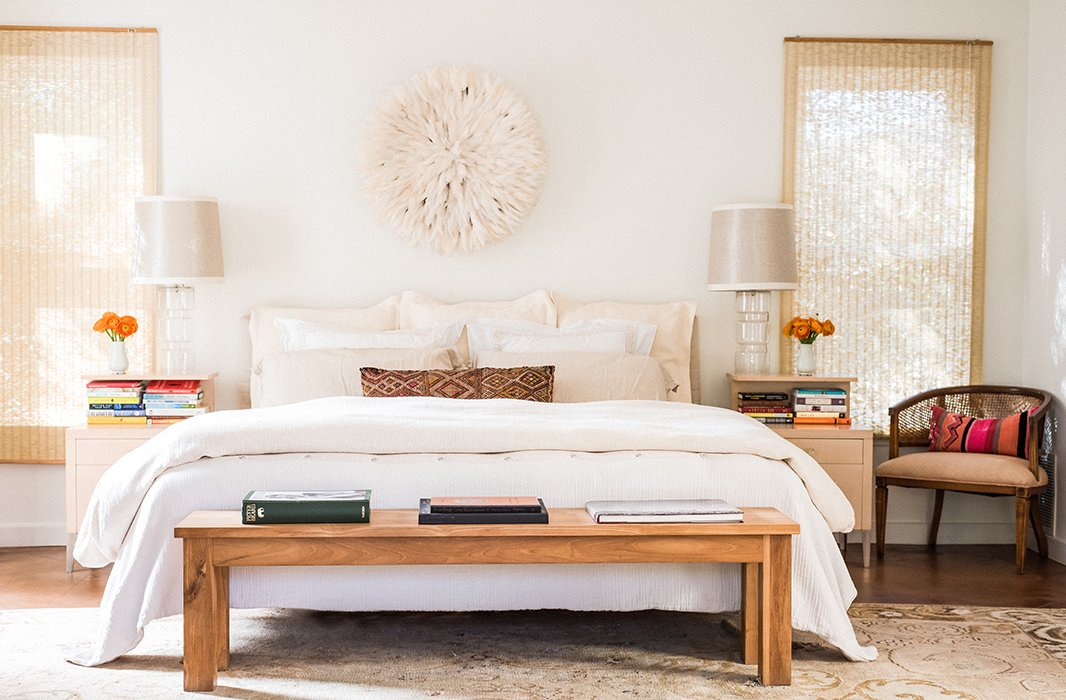 A juju hat flanked by oversize lamps serves as a dreamy focal point in the master bedroom. The wooden bench is an ideal spot to toss throw pillows at bedtime.