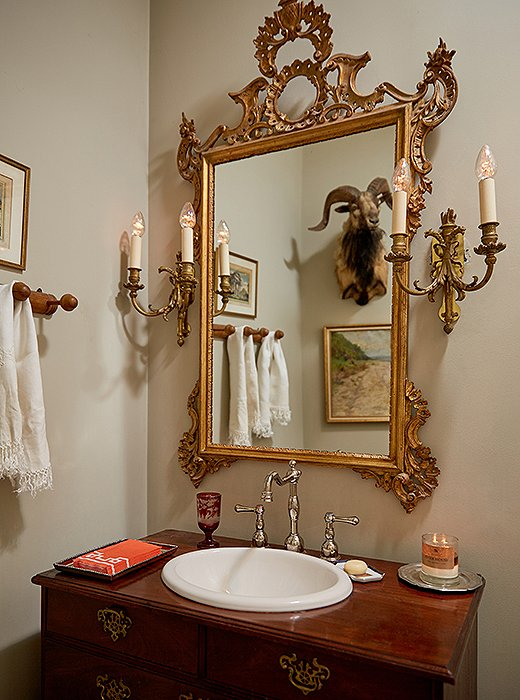 In one of the bathrooms, a Louis XVI mirror layered with gold leaf reflects another taxidermy head. A converted dresser serves as the perfect spot for a ceramic sink and silver fixtures.