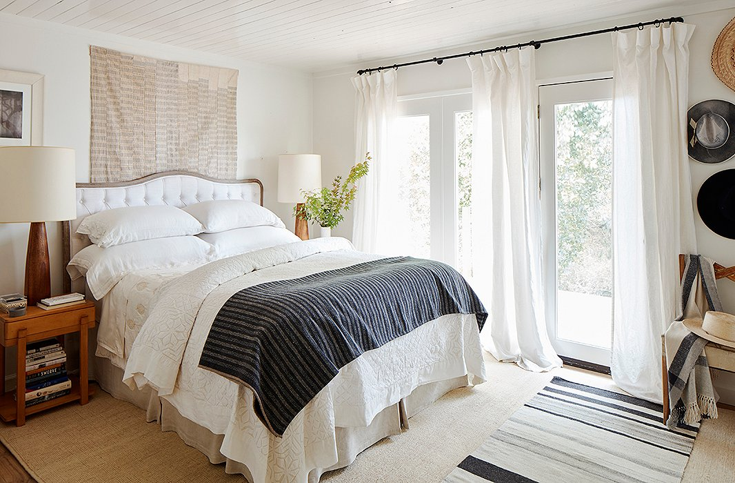 In the master bedroom, an upholstered headboard by Blink is flanked by vintage Scandinavian lamps and Saarinen side tables. Behind, an African textile adds a textural layer of interest and reflects the tones of the room's natural-fiber rug and striped runner.