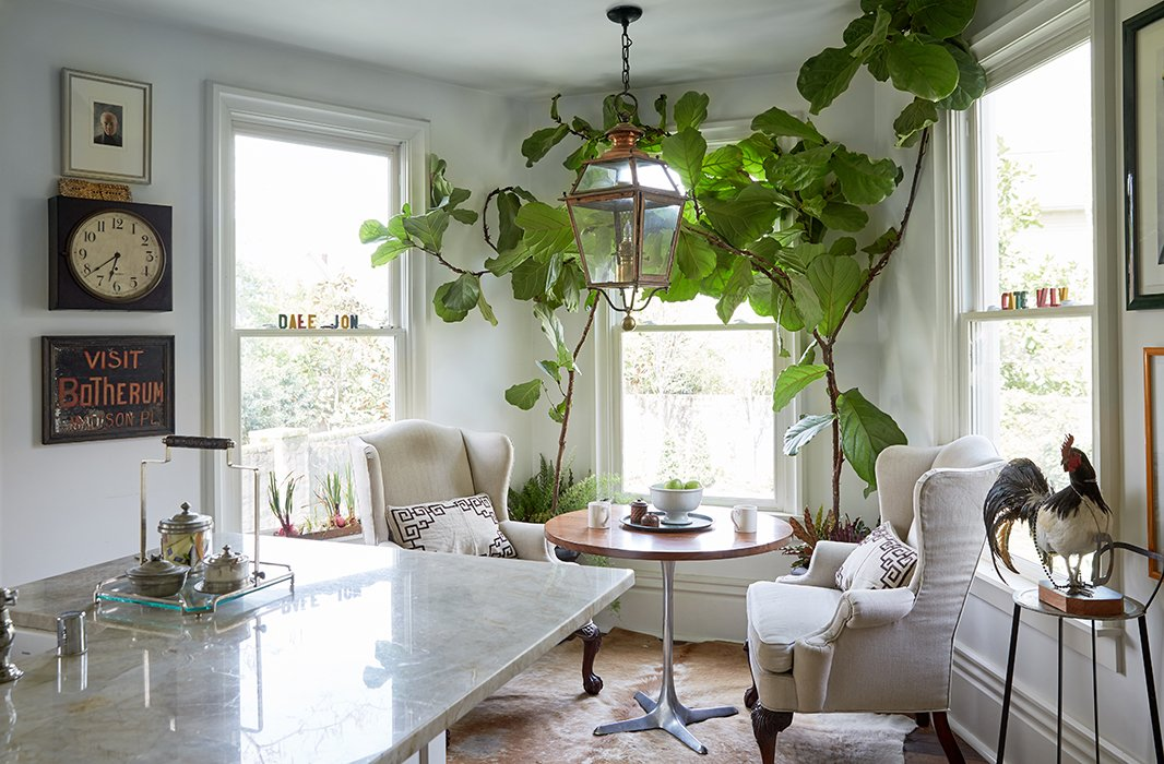 "A window nook allows enough light for a pair of fig trees, under which Jon has his morning coffee and schedules his day. The copper lantern is yet another touch that brings the outside world in. ""I sit here and I get centered,"" Jon notes. ""Looking at the trees blow outside, the sunlight pouring through, I remember what really matters."""