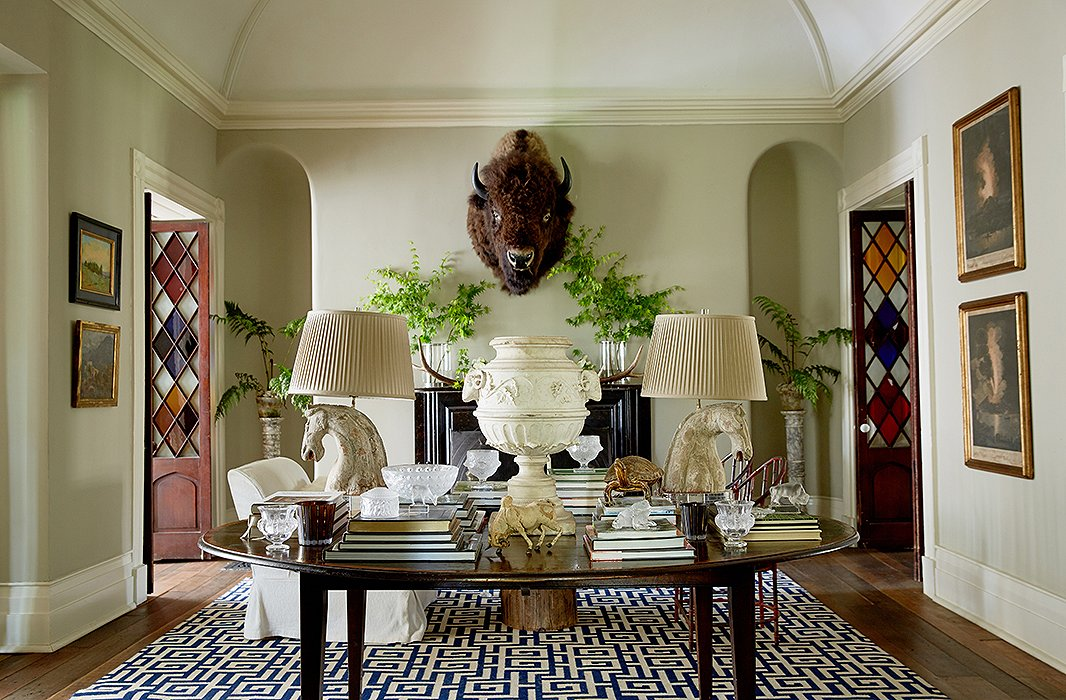 In the foyer, most all is vintage save the blue-and-white rug emblazoned with Greek keys. From between branches (cut from the yard) hangs Otis the bison, watching over a central table stacked with coffee table books and Dale's collection of Lalique glassware. Sculpted stallions crowned by pleated shades flank a marble urn, emphasizing the home's ties to horse country.