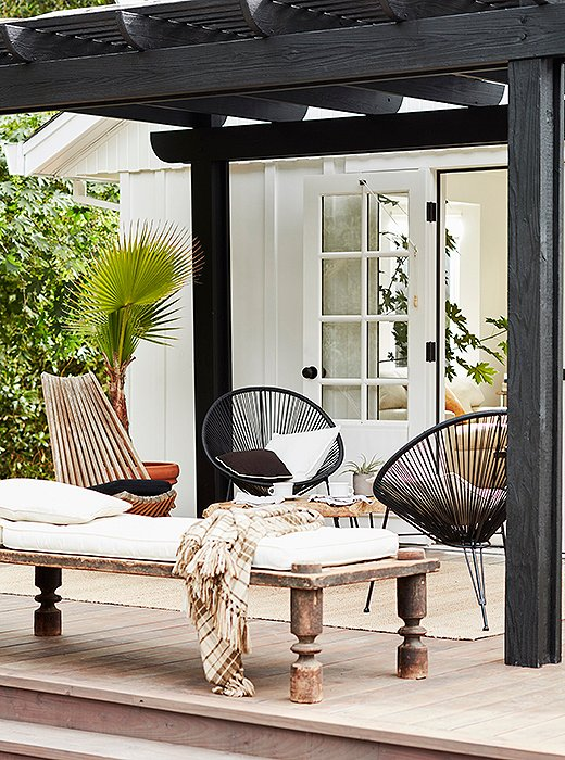 Outside, a black pergola shades a Nepali daybed and folding chair from the '60s.