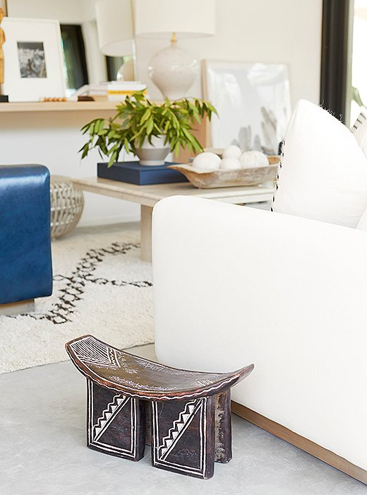 Accents such as a vintage African stool add warmth to the room's cement floors.