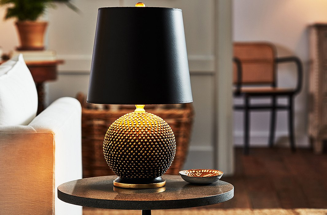 Thanks to its small shape, the Mini Ball Table Lamp (shown here in black with a black shade) is a fitting accent for any space. The details are what really shine on this piece: Gold leaf is hand-applied to the base and every tiny bump, and the shade is lined with a gold finish for an extra luxurious look.