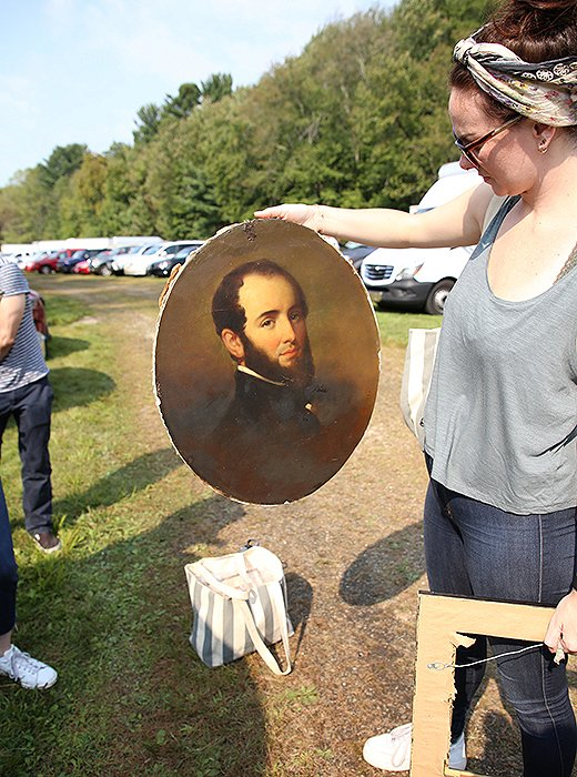 Erika Engstrom takes a closer look at an oil painting the team nabbed before stashing it in the One Kings Lane van. Photo by Taylor Swaim.
