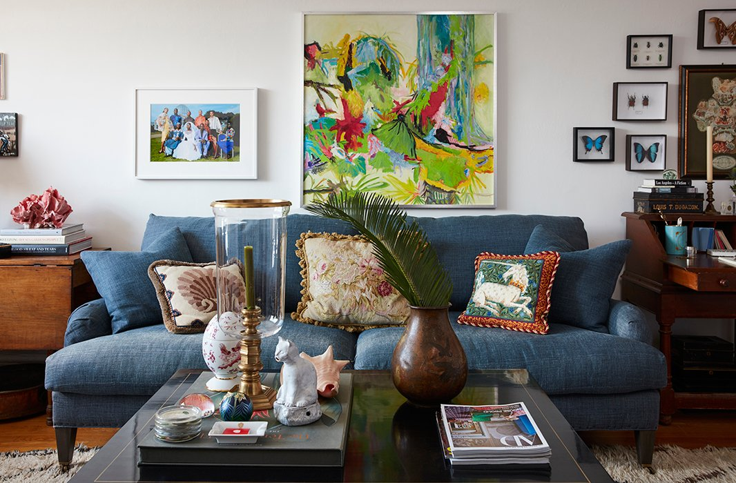 "For Bobby, ""finding the right sofa is like finding that sweater you know you'll have for years—you have to love it."" Here, the couple's indigo sofa anchors an eclectic collection of art, including a painting by Bobby's great-aunt and a photograph from Staley-Wise Gallery, where Matt held his first job."