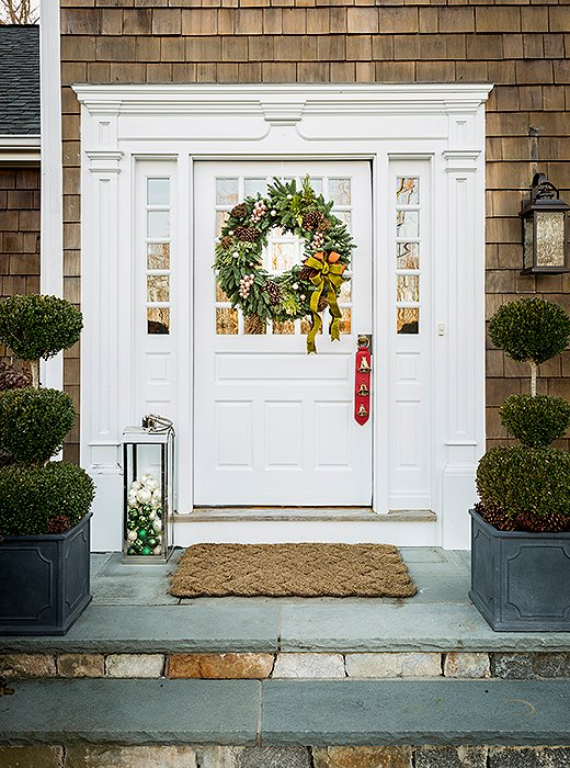 A bow-bedecked wreath and an outdoor lantern filled with ornaments set a festive tone for guests' arrival.