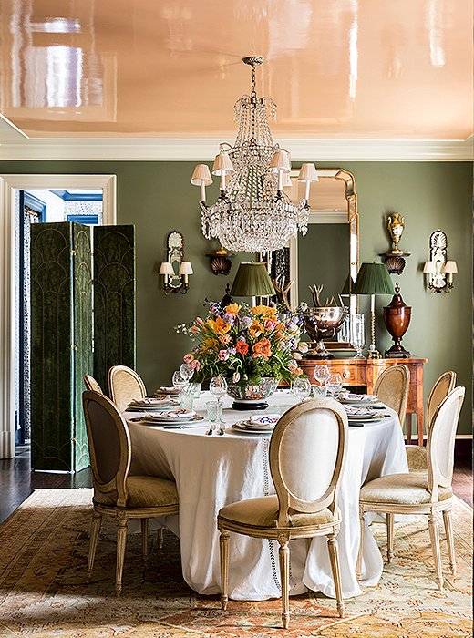 "Louis XVI chairs dressed in velvet encircle a table crowned by an antique chandelier. The combination of the apricot-lacquered ceiling and the dusty green walls creates a flattering glow. ""In the evening, the light that's reflected is just magic,"" Danielle says. ""It's like liquid candlelight."""