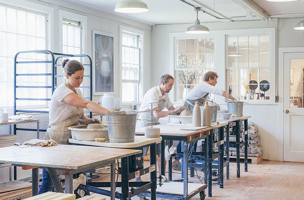 Three potters (including co-owner James Zilian, far right) at work in the Farmhouse Pottery studio. Photo courtesy of Farmhouse Pottery.