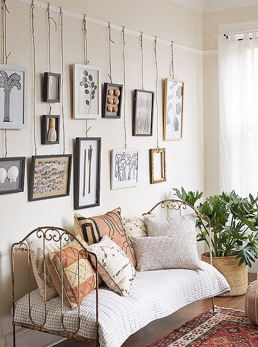 Suspending works by a wire or rope is a chic alternative to the usual way of hanging art.  Photo by Eric Masters.