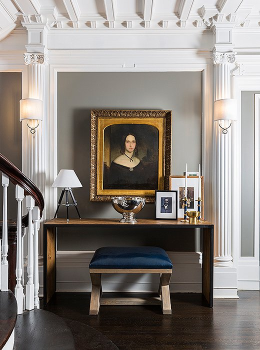 An oil portrait in a gilded frame hangs above a contemporary console by CFC accented with a surveyor-style lamp by Ralph Lauren Home.