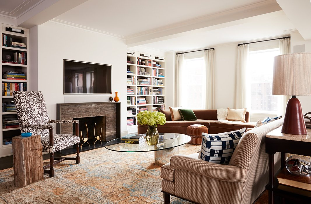 A neutral rug unifies a houndstooth sofa and a patterned armchair, while a glass coffee table offers a modern touch.
