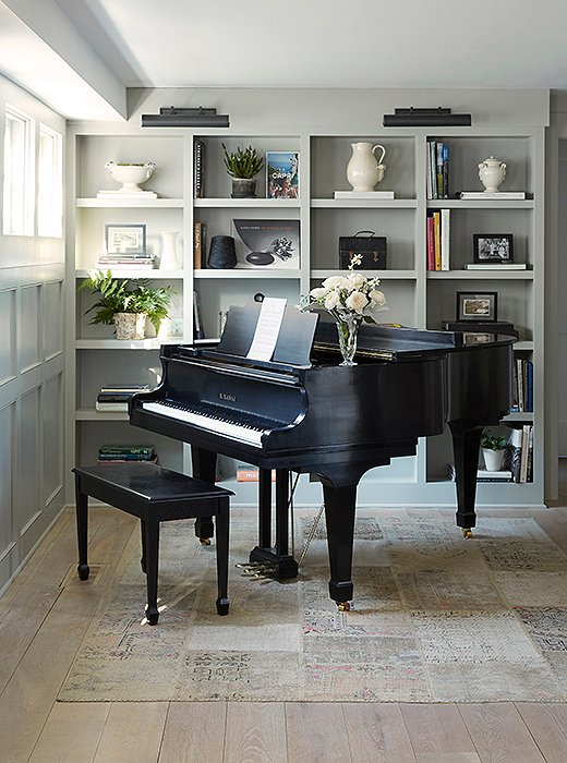 Adding to the homey vibe, a baby grand piano rests on a patchwork rug in front of bookshelves outfitted with library lights.