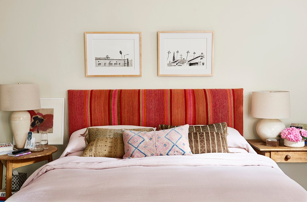 Pink comes into play yet again on the bedroom's headboard, crowned with a pair of black-and-white prints and made pleasantly imperfect with mismatched bedside lamps.