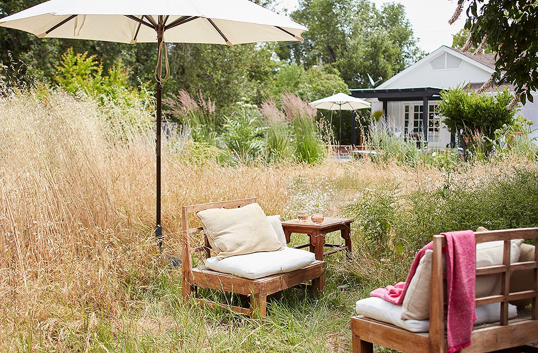 "Beyond the deck is the garden filled with artichokes, sage, lavender, and miscanthus. ""When we moved here from the East Coast, I knew nothing about how to address the plants that were here,"" says Laura, ""so we let it all grow wild, and I love it. Each day I find myself becoming more and more connected with the landscape."""