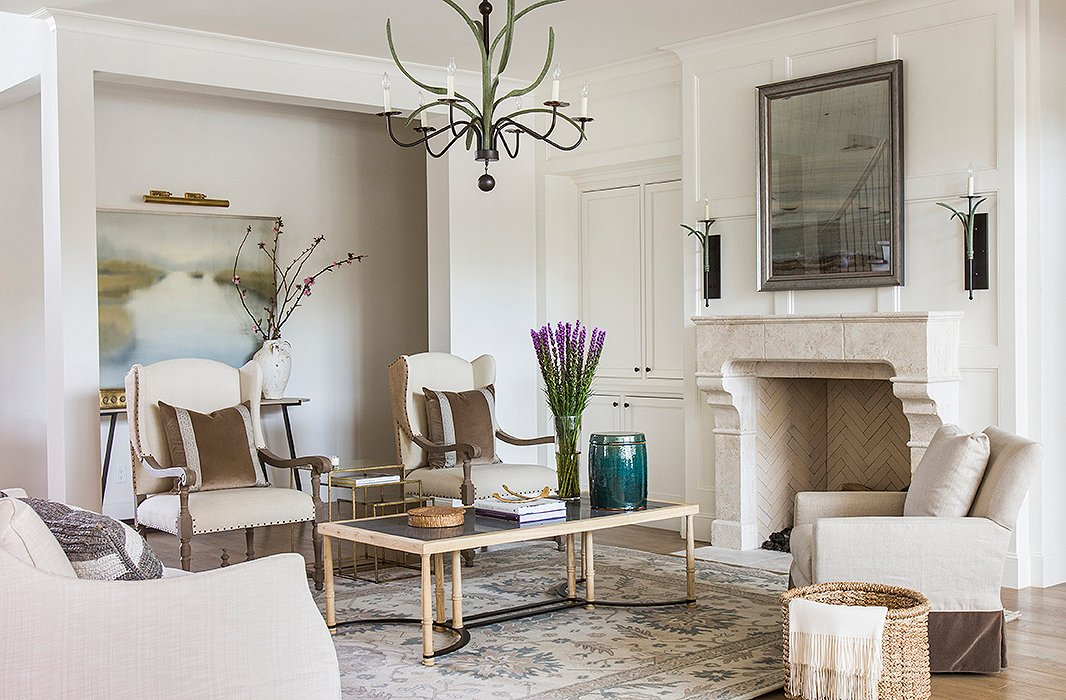 A new stone mantel turned the fireplace into a stunning focal point for the living room, which was dressed in soft tones of brown and blue. Marie's firm worked with The LaRocque Group on the remodel. Photo by Julie Soefer.