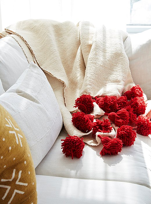 A tasseled throw adds texture and vibrancy to a neutral base.