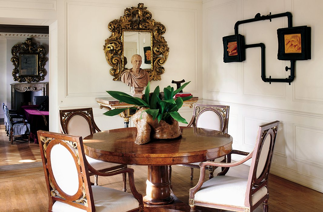"""I loved seeing rigorous modern art played off against frescoed walls, warped wooden beams, and worn stone floors,"" writes Richard, who anchored his breakfast room with 18th-century giltwood chairs, a reproduction burlwood table, and a contemporary sculpture by Jeanne Silverthorne."