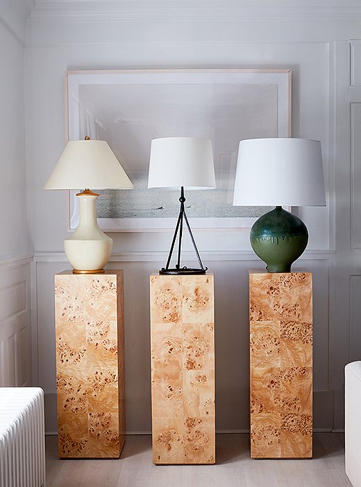A trio of burl-wood pedestals shows off a selection of table lamps.