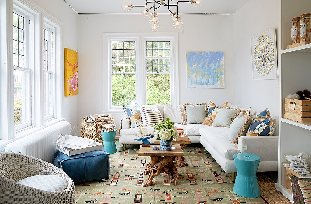 A table made of driftwood brings the seaside inside. Garden stools and artwork add color and pattern, complementing the pinks and blues found in the flat-weave rug.