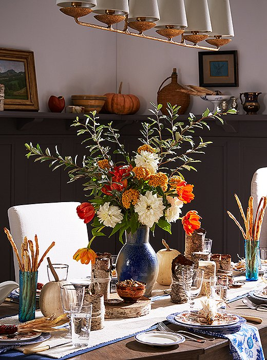 White dahlias, orange parrot tulips, ocher coxcombs, and a seasonal branch make up this lush, fall-feeling flower arrangement.