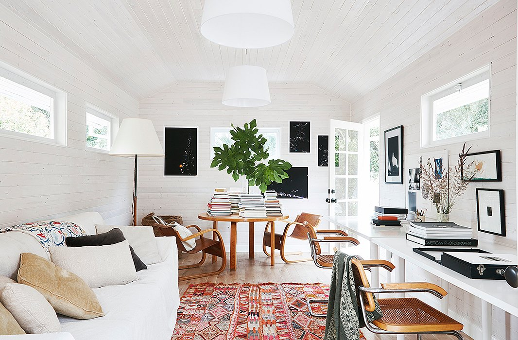 What was once a gray space with limited light was transformed into a loftlike studio. Toward the rear, a round Alvar Aalto table matches the tone of the Breuer desk chairs and keeps stacks of coffee table books at the ready.