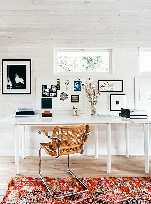 A Marcel Breuer armchair featuring a hole-in-cane pattern complements the desk of photographer Laura Resen. One could say it adds warmth to the space in the same way a woven handbag adds warmth to a white suit and Prada pumps.