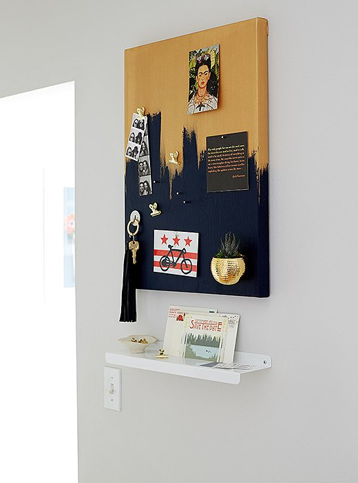 Anthony created a DIY magnetic board and a slim shelf for Ari to set her keys and hang reminders. The board also cleverly conceals the apartment's circuit breaker.