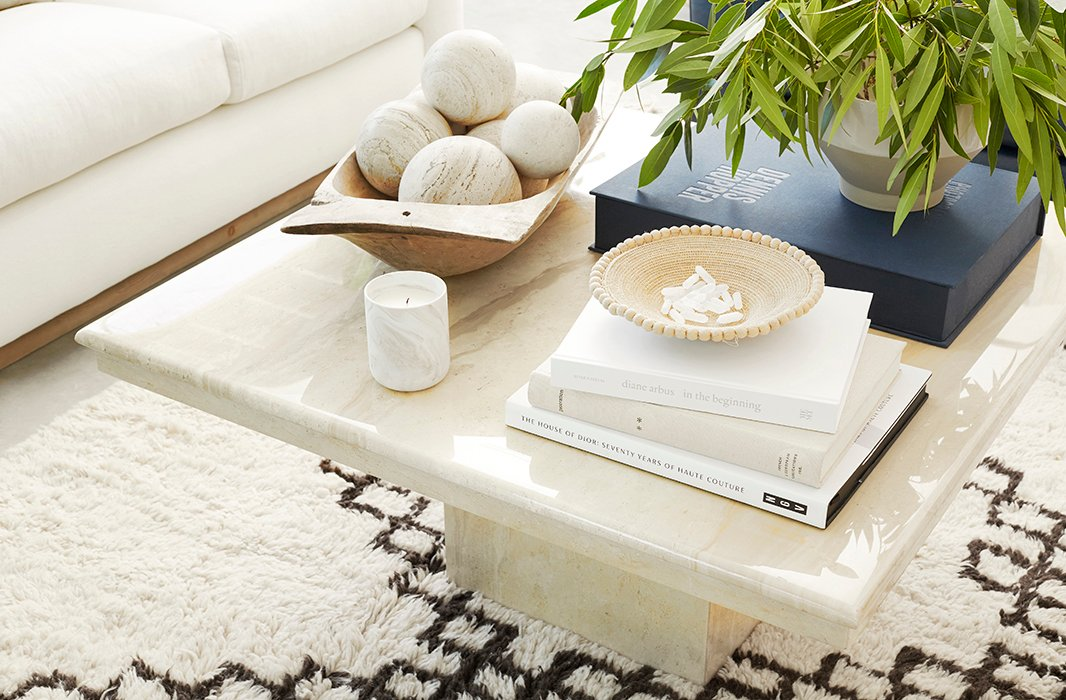 An Italian travertine coffee table from the 1970s brings a sense of polish to the laid-back space. On top, a French dough bowl was filled with a set of spheres selected to match the tone of the table's stone.