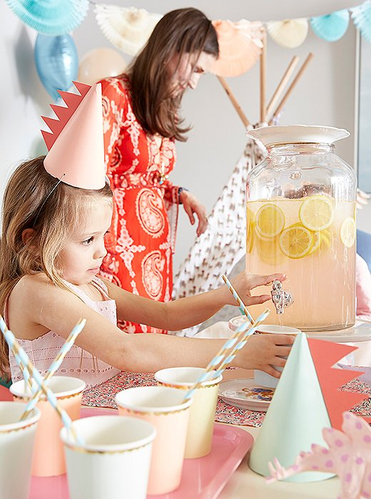 A pretty drink dispenser lets older partygoers help themselves. Recyclable paper cups and straws keep the palette consistent (and make for easy cleanup).