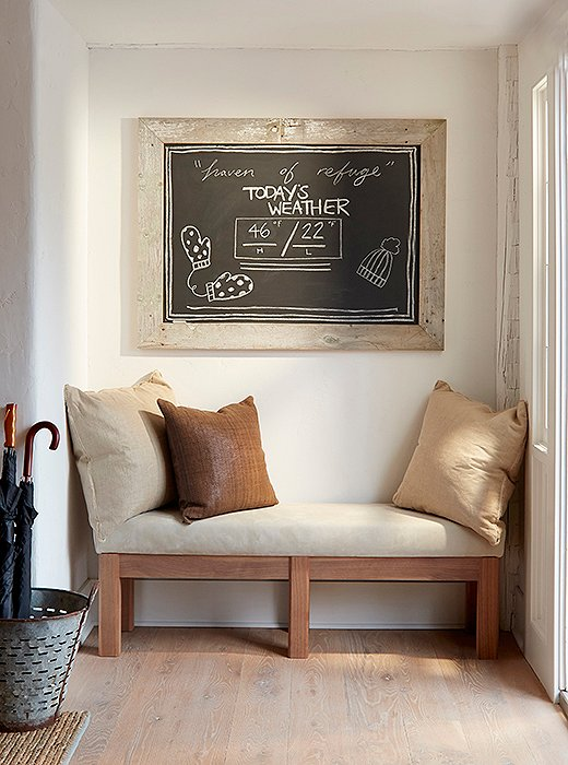 In the lobby, a chalkboard displays the day's forecast above a bench ideal for taking off Wellingtons.