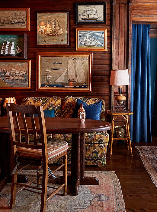 "In the bar's lounge, flame-stitch-covered sofas make an unexpected counterpoint to a salon-style display of nautical artwork, including framed wool-stitched scenes, or ""sailor's woolies,"" found at Nantucket antiques shops."