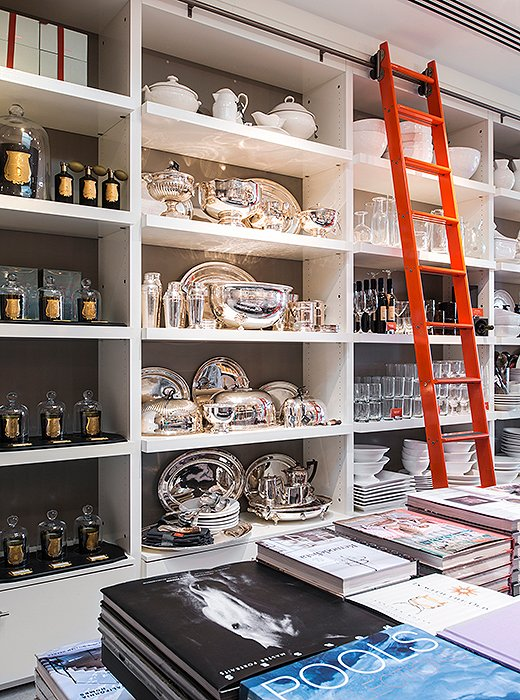 A library ladder painted in International Orange, the color of the Golden Gate Bridge, adds a playful pop to the gray-and-white Montecito store interior.