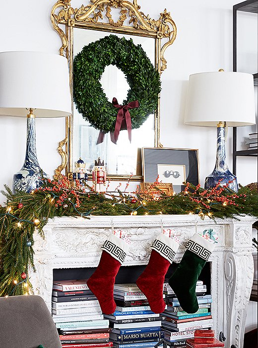 A pair of marbleized lamps feel decidedly daring on the classic Christmas mantel, contrasting nicely with the traditional gilded mirror and beribboned boxwood wreath.