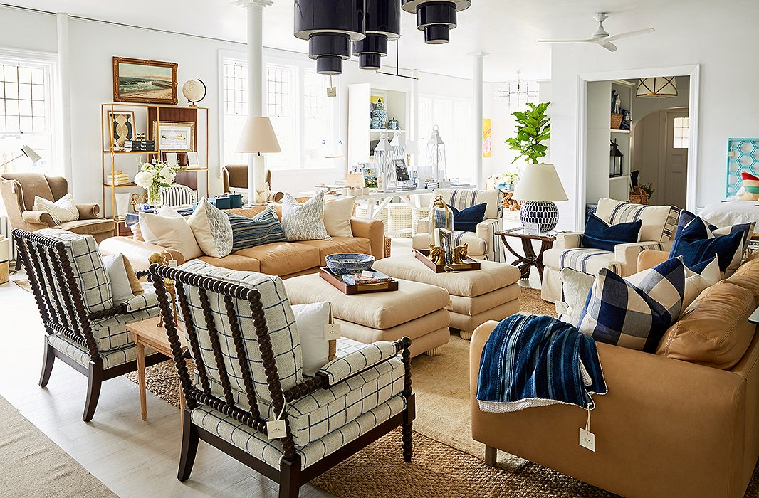 A living area in neutral hues featuresspindle chairs by Miles Talbott, vintage accents, and cylindrical pendantsinspired by the Swinging '60s.